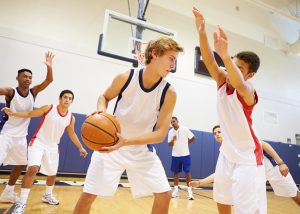 Image shows males playing indoor basketball