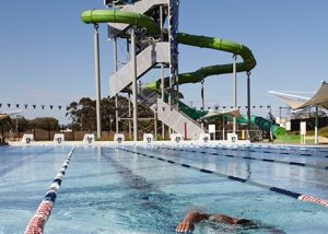 Image shows outdoor swimming pool with giant outdoor enclosed water slide in bcakground