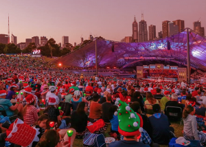 Image shows Vision Australia's Carols by Candlelight in the Sidney Myer Music Bowl with patrons watching the on stage entertainment