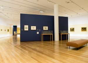 Image shows interior of art gallery with paintings on display