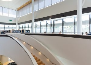 Interior of Bunjil Place Library with state of the art design and wide staircase showing the library split over multiple levels
