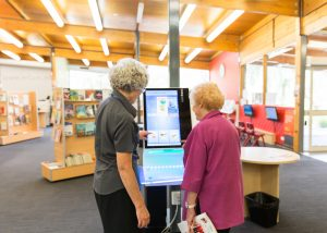 Interior of Ferntree Gully Library showing staff assiting member with borrowing items