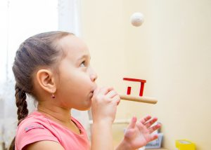 Young girl using a speech therapy device to practice blowing