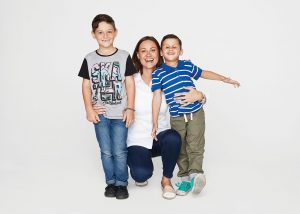 Young mother with two sons hugging and smiling