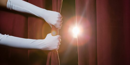 Pair of hands wearing long white gloves parting a pair of theatre curtains to reveal a spotlight