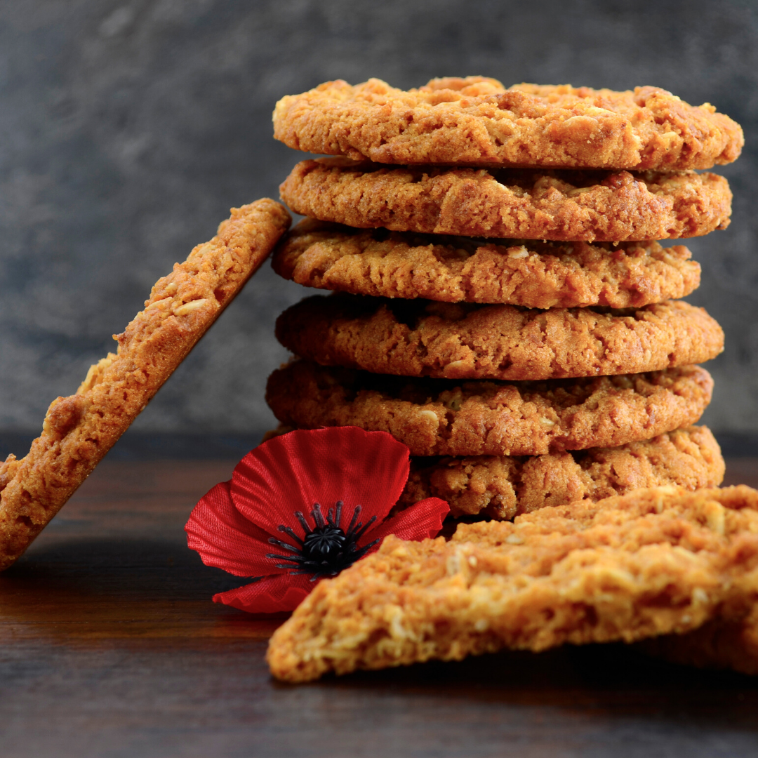 A stack of ANZAC biscuits and a red poppy