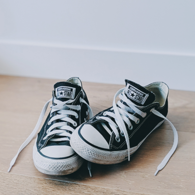 Pair of black converse shoes sitting on wooden floor with laces untied