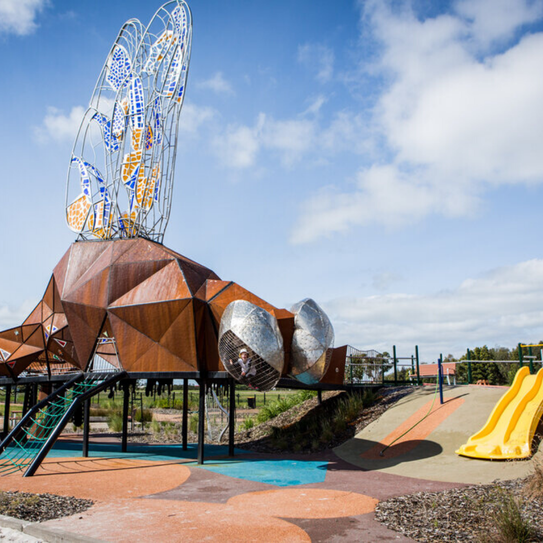 Giant Dragonfly in centre of playground next to yellow slide