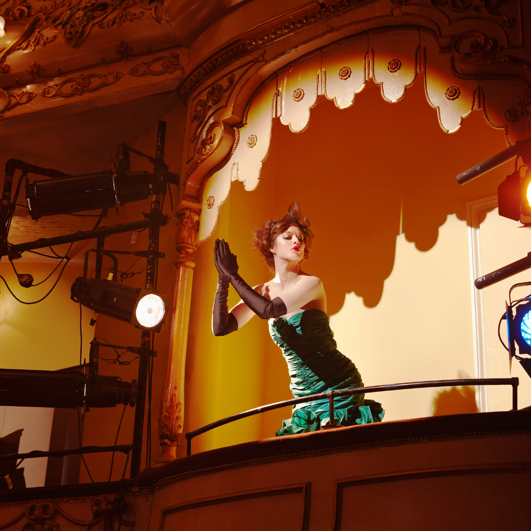 Lady standing in a theatre booth applauding performance