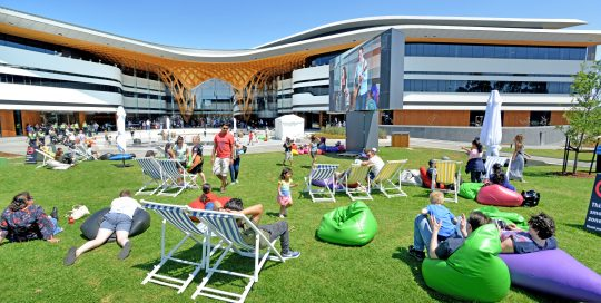 Image shows exterior of Bunjil Place Plaza with grass and people relaxing in deck chairs and beanbags in the sunshine