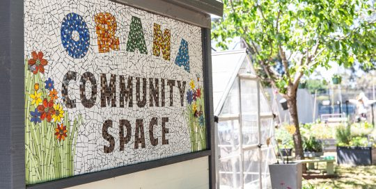 Mosiac tiled signage with words Orana Community Space and a greenhouse and gardens in the background