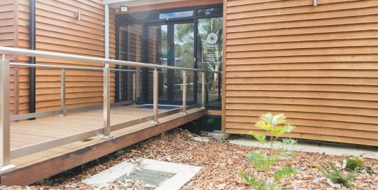 Image shows exterior of The Basin Community House with entry/exit point and access ramp
