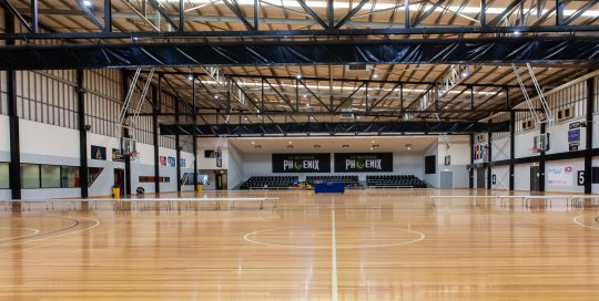State Basketball Centre showcourt with wooden floor, player bench seating and blue spectator tiered seating