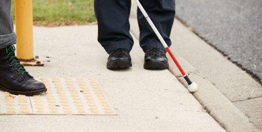 Person using a white cane standing next to tactile ground surface indicators at a road crossing