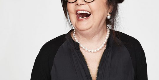 Middle aged lady wearing glasses and laughing