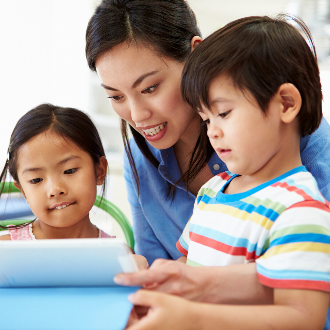 Mother with two small children, a boy and a girl, looking at an iPad