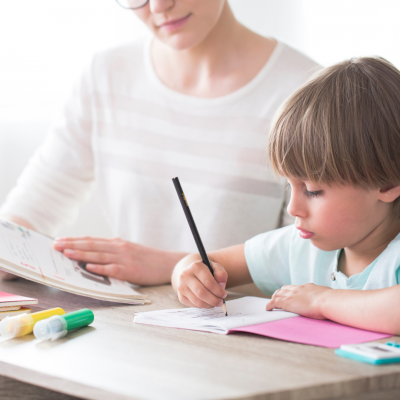 Young boy learning to write sitting at desk with mother