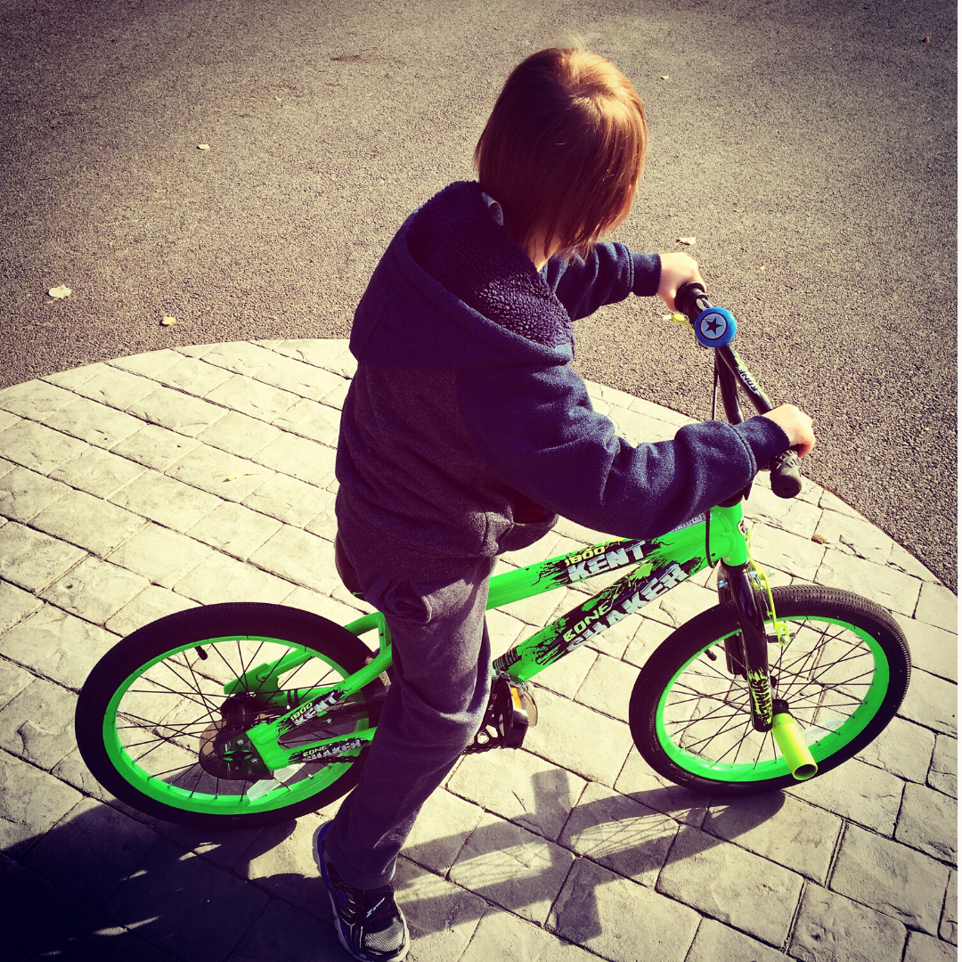 Young boy riding a green bike outdoors