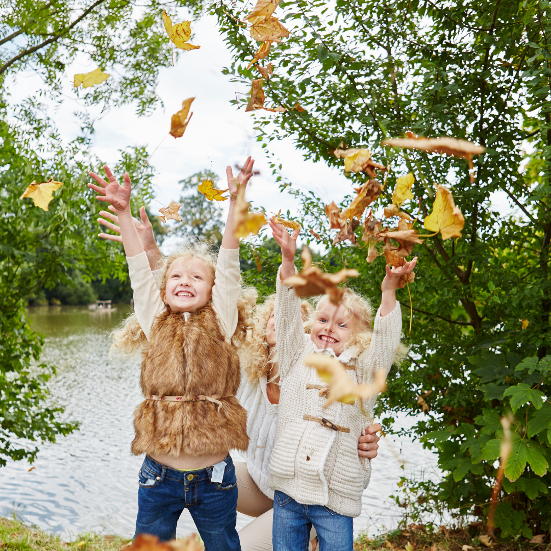 Two young girsl and a mother outdoor throwing autumn leaves in the air
