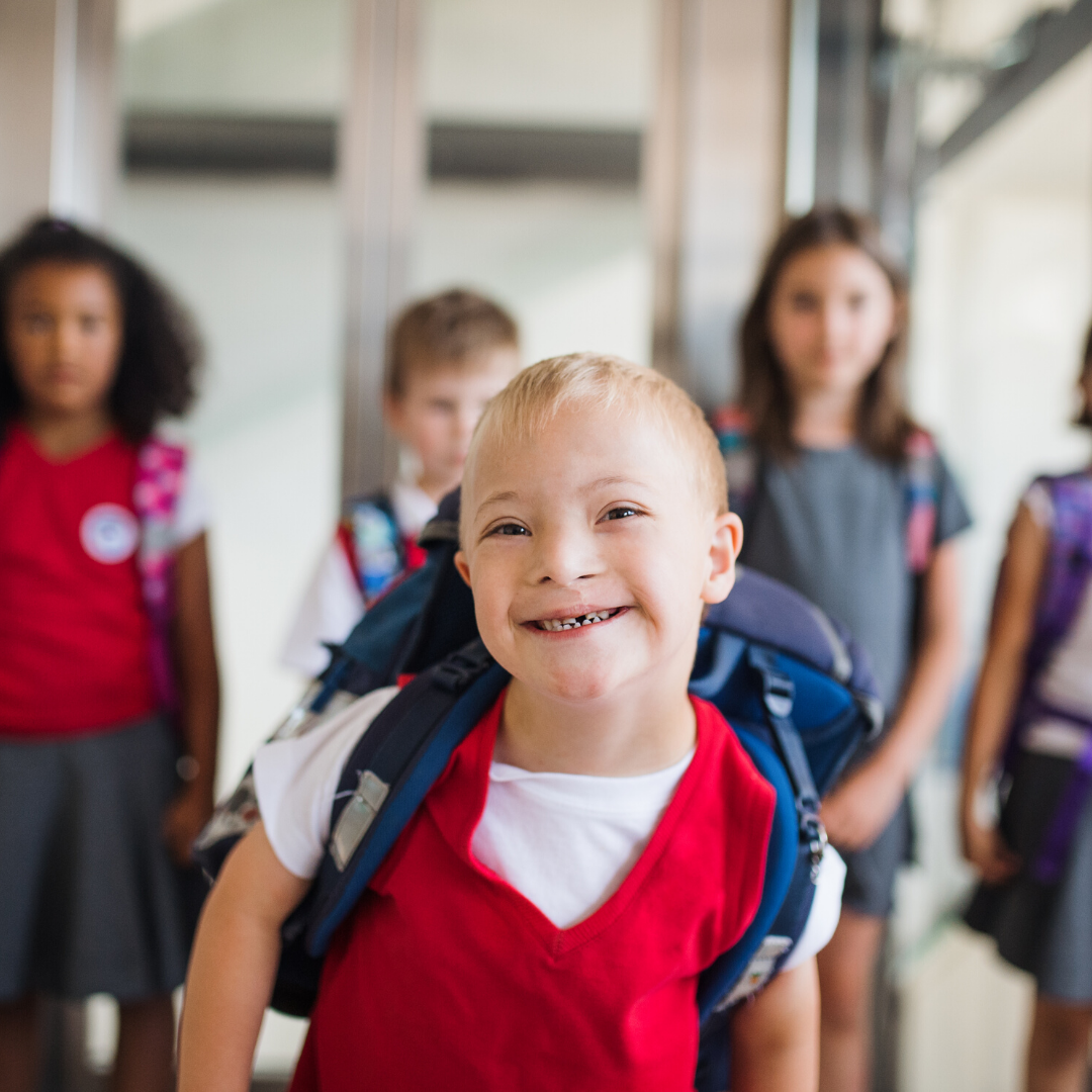 Young boy with school bag in school hallway with friends