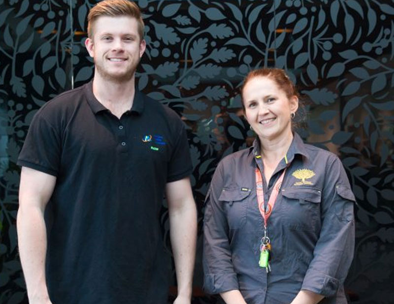 Young adult male wearing a black shirt with Access Ability Australia branding standing next to an adult female dressed in a grey shirt with Royal Botanic Gardens Victoria branding