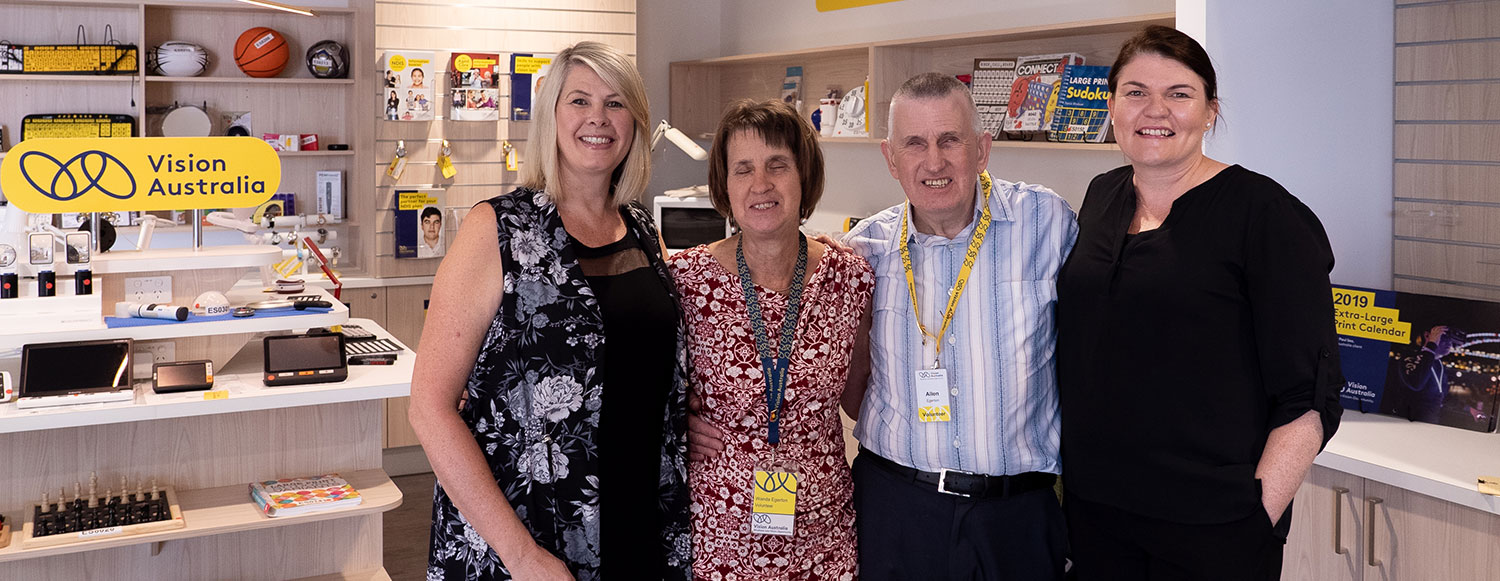 Three adult females and one male standing closely together in a Vision Australia office with adaptive shop equipment in the background