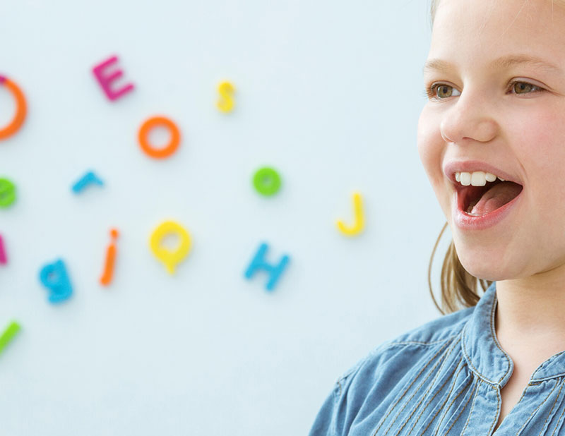 Picture of young girl practising letter sounds with colourful letters displayed on the wall behind her