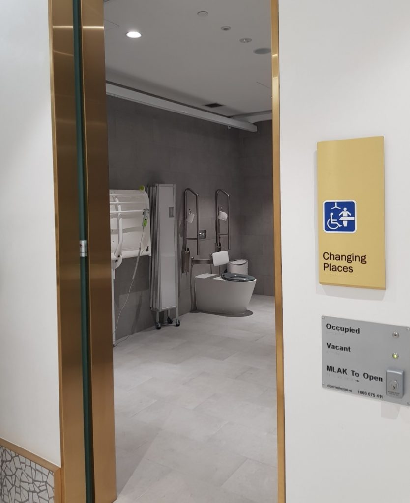 Exterior of a Changing Places facility showing signage on the outer and the interior facility