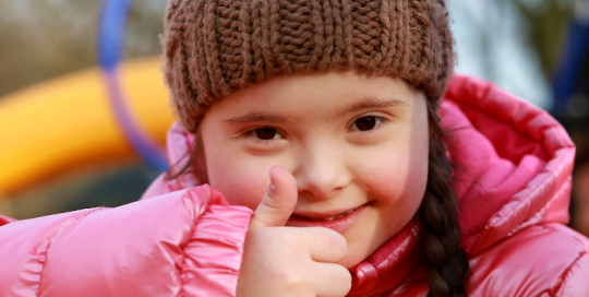 Young girl with disability in a playground giving a thumbs up