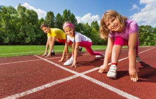 Three children at starting line of athletics running track