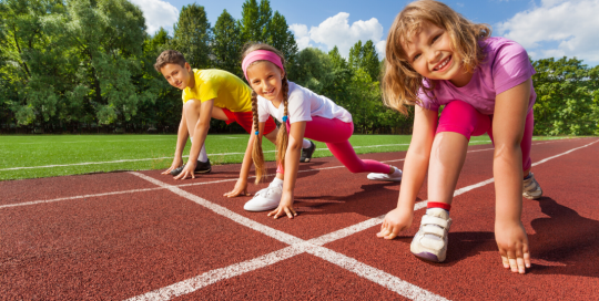 Three children at starting line of athletics running track
