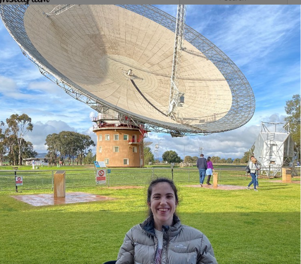 Young lady seated in wheelchair pictured in front of large satellite dish