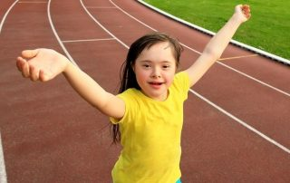 Young girl with Down Syndrome wearing bright yellow t-shirt and running on an athletics track with arms in the air and an happy expression on her face