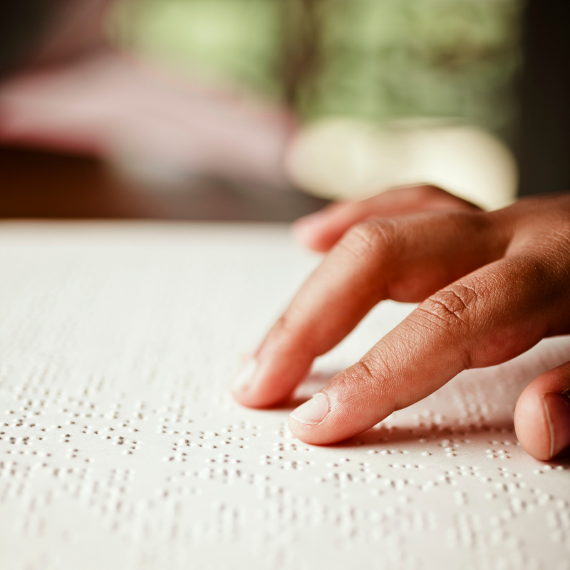 Person's fingers reading Braille
