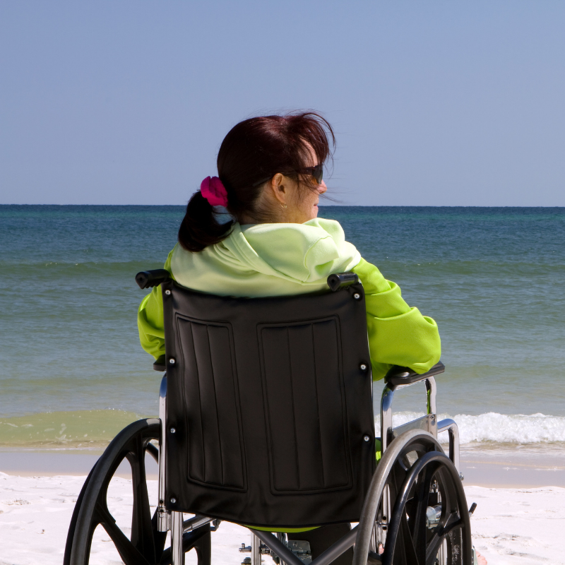 Adult female sitting in a wheelchair at the beach
