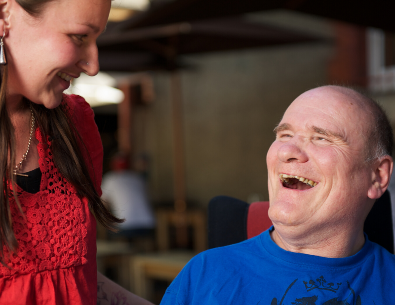 elderly gentleman sitting in a chair smiling whilst communicating with an adult female