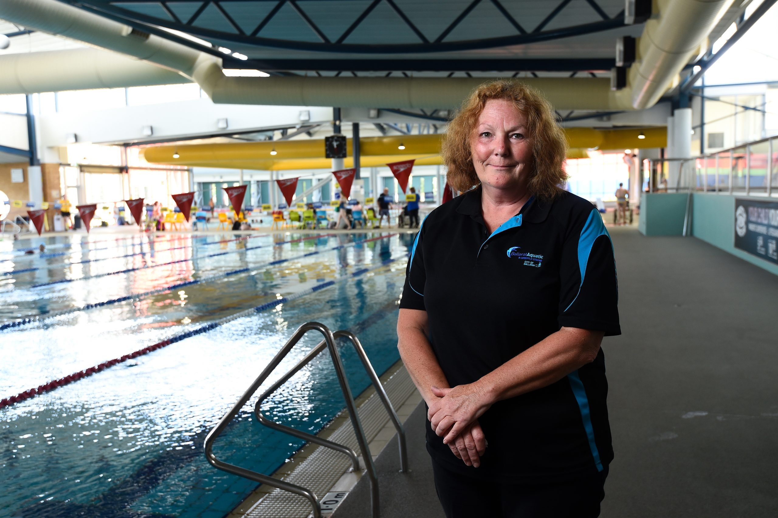 Female staff member standing in front of indoor swimming pool at Ballarat Aquatic and Lifestyle Centre