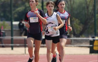Three young girls dressed in athletic gear running on an athletics track