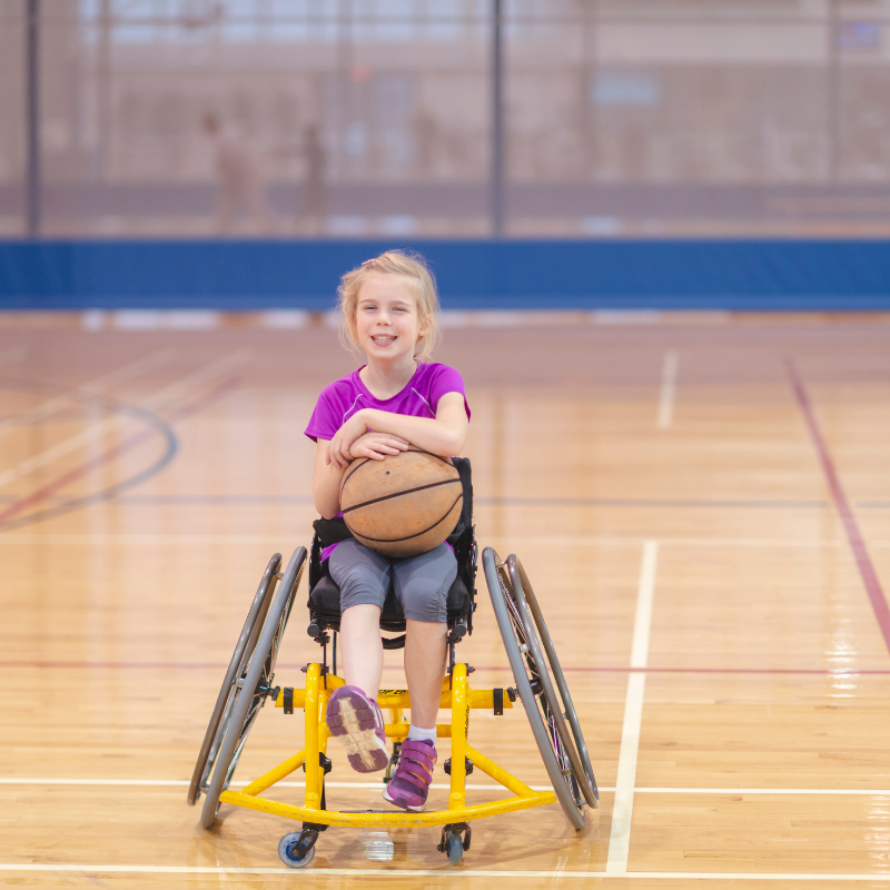 Young girl in wheelchair on indoor basketball stadium holding a basketball