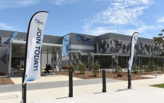 Exterior front entrance to Gurri Wanyarra Wellbeing Centre with branded flags and a blue sky