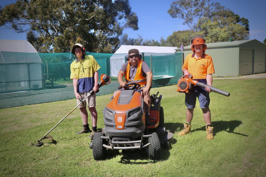 Three young adult Walalra clients pictured outdoors working in the gardens of Sages Cottage Farm