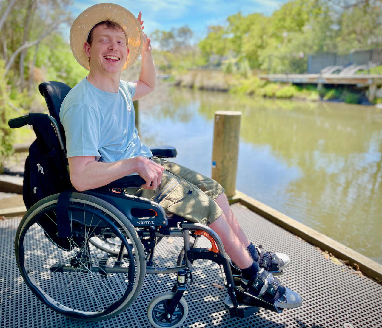 Young adult male in wheelchair waving pictured outdoors at Cranbourne Royal Botanic Gardens