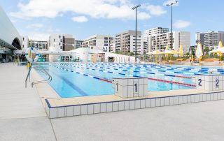 Gunyama Park outdoor 50m swimming pool with lane ropes. City buildings in the background.