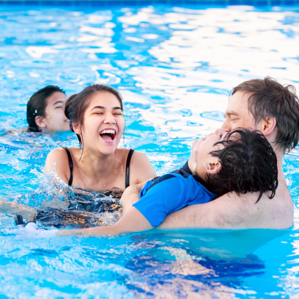 Young boy with disability swimming with family