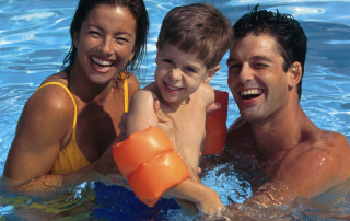 Family of mum, dad and small boy all smiling and swimming