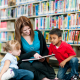 Adult female sitting on floor with two children in a public library sharing a book together