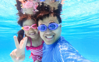 Male adult and young female child playing in the water. Both wearing goggles and smiling.