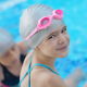 Young girl wearing bathers, swimming cap and goggles sitting on edge of pool
