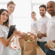 Young males and females volunteers packing food parcels