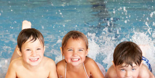 Three young children featured on the side of an indoor swimming pool partaking in a swim lesson